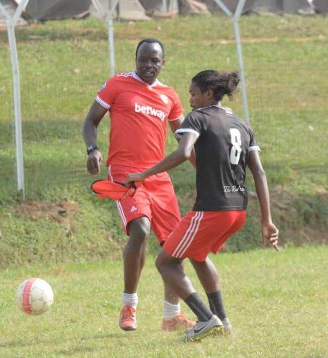Ssemwogere (L) challenges assistant captain John Revita in training