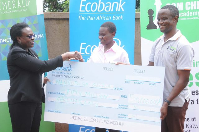 Ecobank's executive director Annette Kihuguru (left) handing Gloria Nansubuga a dummy cheque as Robert Katende (right) looks on at the launch in Makindye. Photo by David Namunyala