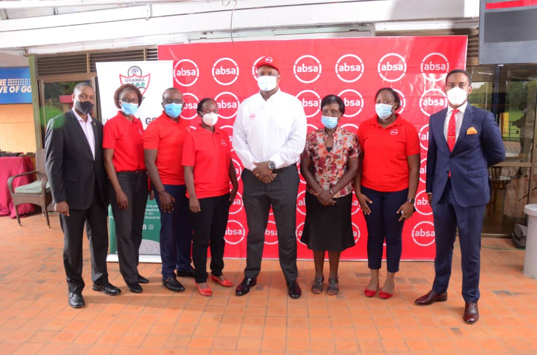 Absa's Kalifungwa (white top), UGC's Ruth Ssali (3R) flanked by staff from the bank (red tops) and the club members on Tuesday