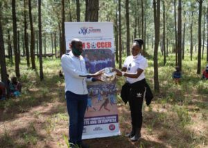 CEO Ritah Aliguma hands over balls to the area chairman Godfrey Isingoma (L) as a symbol to show that the foundation is all about sports and enterprise.