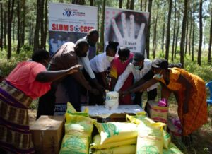 Ritah Aliguma (middle) is joined by some locals in a cake-cutting session to cap the event
